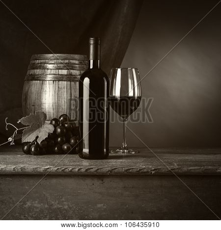 Red wine tasting with bottle wineglass barrel and grape on the cellar wooden table red drape on background still life poster