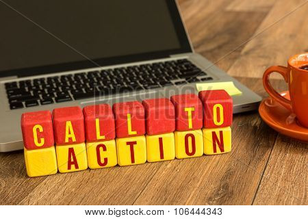 Call to Action written on a wooden cube in front of a laptop
