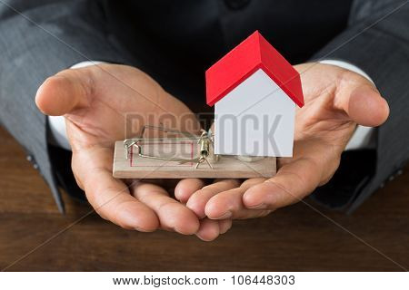 Businessman Holding Model House On Rattrap