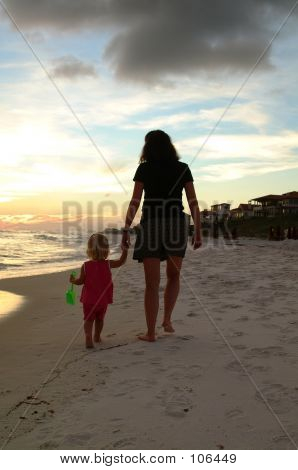 Mom And Daughter Walk On The Beach