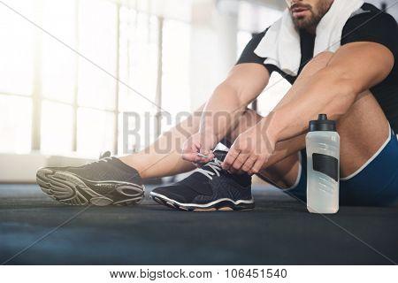 Sportsman ties his black sneakers