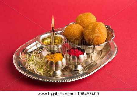 Beautifully Decorated Pooja Thali for diwali celebration to worship , having Indian sweet motichoor