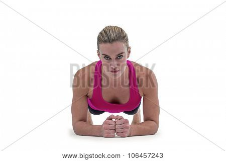 A muscular woman on a plank position on white background