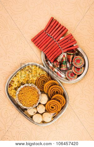 diwali food or diwali snacks or diwali sweets with diwali fire crackers in silver plate icolated on