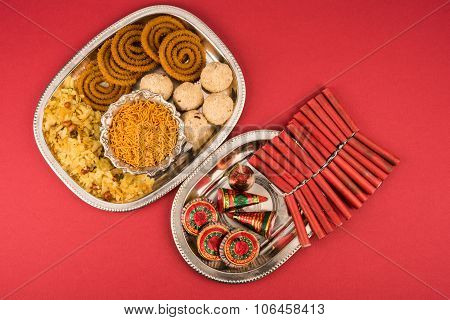 Diwali snacks with Diwali fire crackers in silver plate isolated on red background