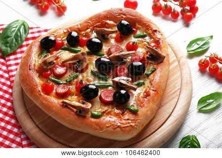 Heart shaped tasty pizza and red checked cotton serviette on wooden background