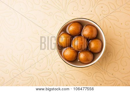 Gulab Jamun served in a round ceramic bowl - An Indian sweet dish, round shaped, black or brown text