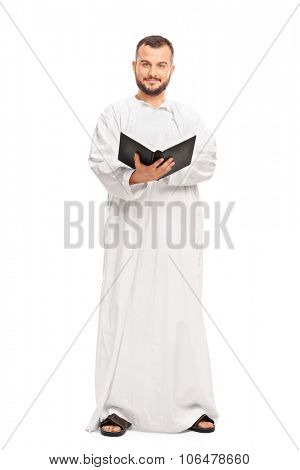 Full length portrait of a religious man in a white robe holding a holy book and looking at the camera isolated on white background