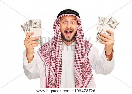 Excited young Arab holding few stacks of money and looking at the camera isolated on white background