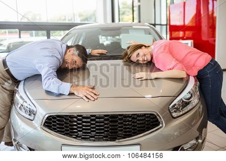 Casual smiling couple hugging their new car at new car showroom