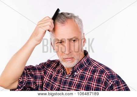 Upset gray aged man combing his hair poster