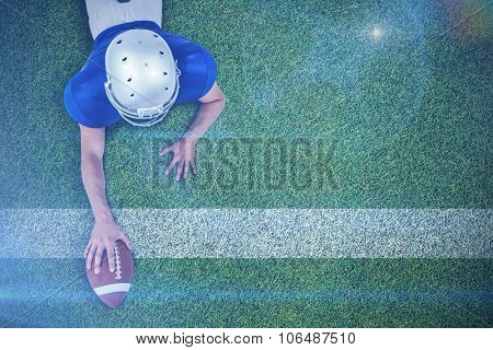 American football player lying in front with ball against pitch with line