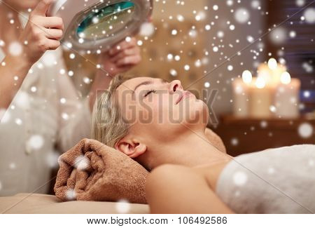 people, beauty, skin care, winter and relaxation concept - close up of beautiful young woman lying with closed eyes and beautician looking through magnifying lamp in spa salon with snow effect