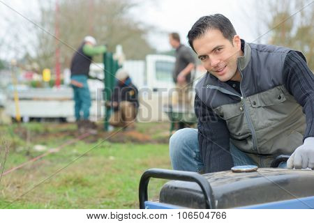 Builder kneeling by a generator