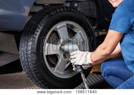 Midsection of female mechanic using pneumatic wrench to fix car tire at repair shop poster