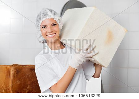 Portrait of confident female baker carrying big bread loaf in bakery