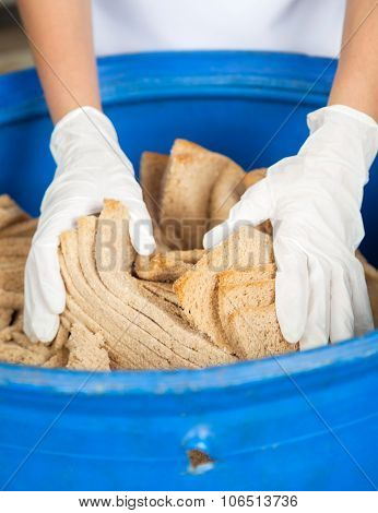 Closeup of woman's hands discarding bread waste in garbage bin at bakery