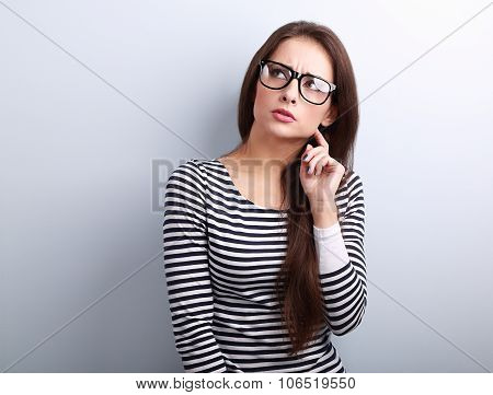 Annoyed angry young woman in eyeglasses thinking and looking up on blue background poster