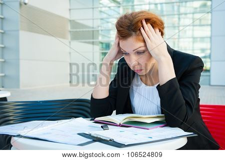 Frustrated and tired business woman sitting in modern background poster