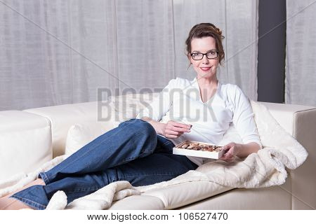 Attractive Woman On Couch Eating Chocolate