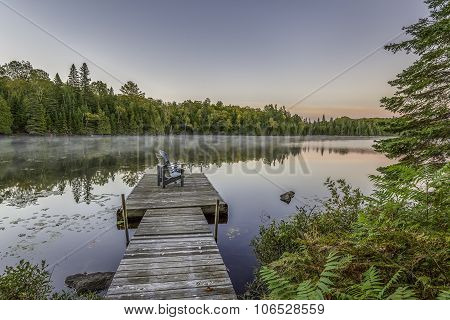 Dock And Chairs On A Lake At Sunset