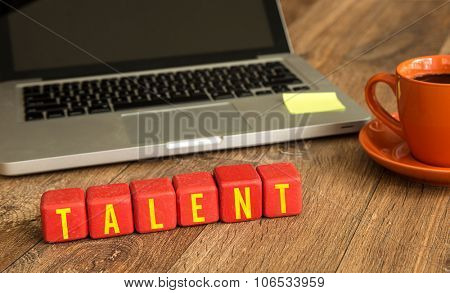 Talent written on a wooden cube in front of a laptop