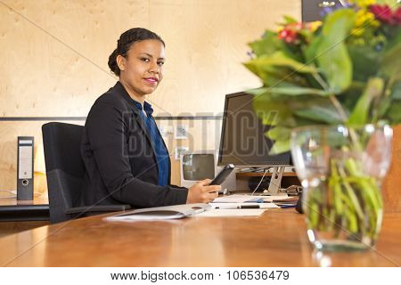 Young security guard manning the front desk of a large company during the night shift, with a computer monitor and cctv monitor, holding a phone. poster