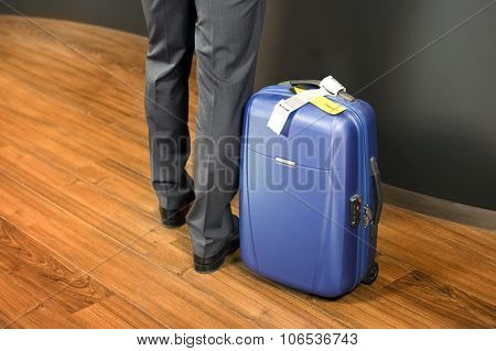 Business class passenger, with a carry on suitcase with priority luggage tags standing at an airport check-in counter