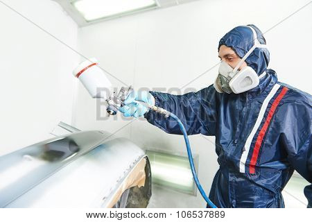worker painting auto car bumper using spray gun in a paint chamber during repair work. Focus on pulverizer