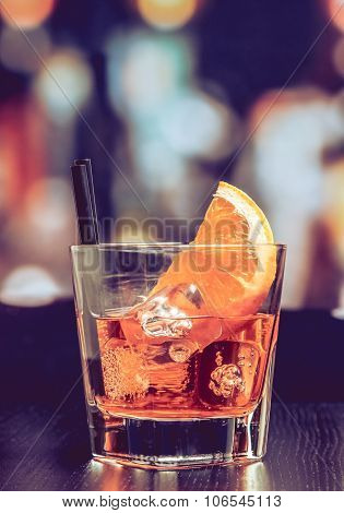 Glass Of Spritz Aperitif Aperol Cocktail With Orange Slices And Ice Cubes On Bar Table, Vintage Atmo