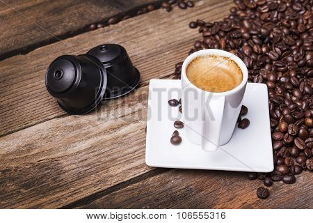 Cup of coffee and pods on wooden table poster