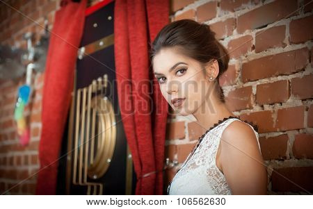 Charming young brunette woman in white lace blouse near a red brick wall. Attractive gorgeous girl