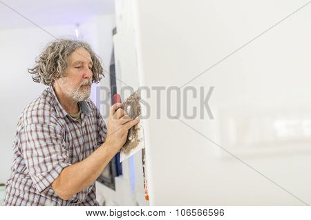 Older Man Plastering A Wall As He Fixates An Orange Corrugated Plastic Cable Duct