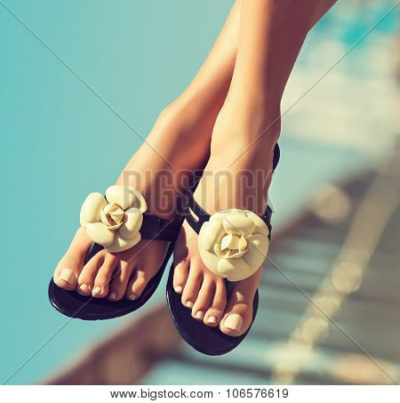 Elegant girls legs pedicure with the nails . Graceful female feet in beautiful flip flops on the bea