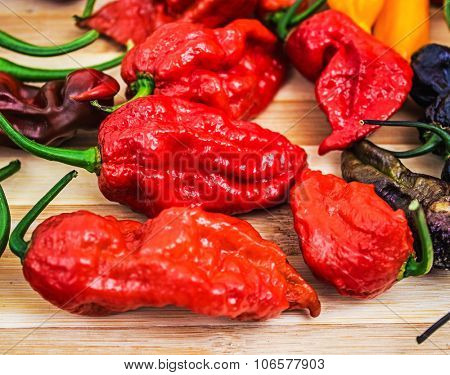 Various very hot chili peppers on wooden table, habanero, scorpion, moruga, jolokia