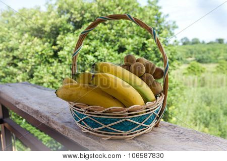 Bananaas fruits in wood basket on nature background