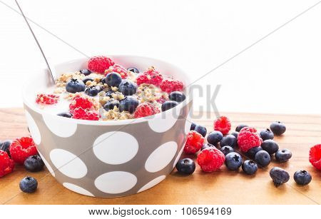 This is a healthy breakfast composed of cereals in milk with rasberries and blueberries