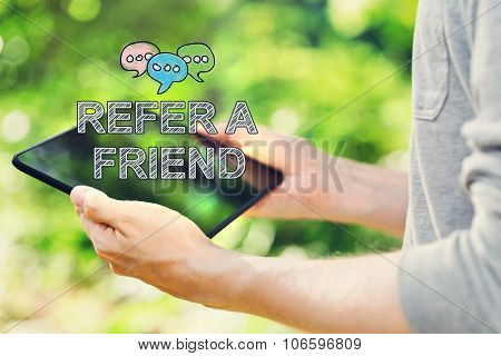Refer A Friend Concept With Young Man Holding His Tablet Computer