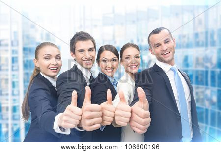 Group of thumbing up business people, blue background. Concept of teamwork and cooperation