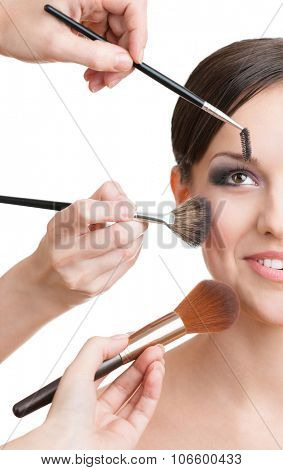 Three hands of makeup artists applying cosmetics on the beautiful woman's face