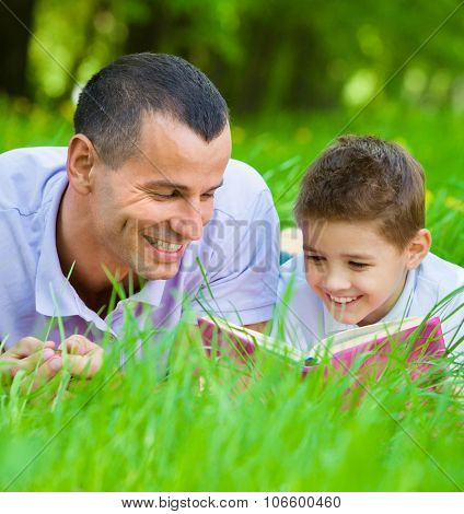 Father and son reading book lying on green grass in park. Concept of happy family relations and carefree leisure time