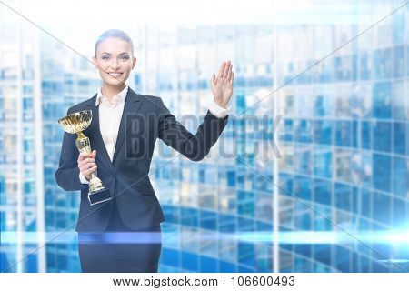 Portrait of businesswoman keeping golden cup and waving her hand, blue background. Concept of victory and success