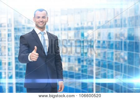 Portrait of businessman thumbing up, on blue background. Concept of leadership and success