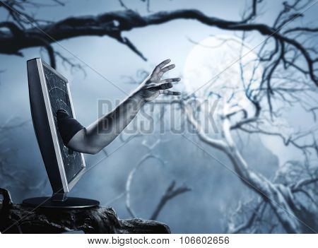 Male hand rising from computer screen in the horrific forest