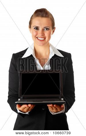 Smiling modern business woman holding laptop in hand with blank screen