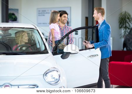 Family with friendly car dealer in car showroom choosing car