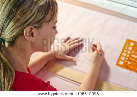 University student of Interior Design doing homeworks completing housing project for final exam. The girl draws lines on a blueprint with a rule in her studio. Selective focus on eye High angle view poster
