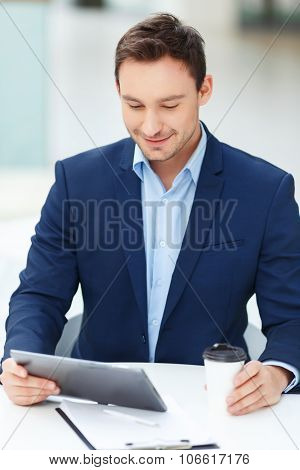Young gentleman with tablet and papercup of coffee.