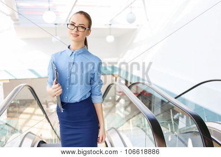 Office employee with clipboard near escalators.