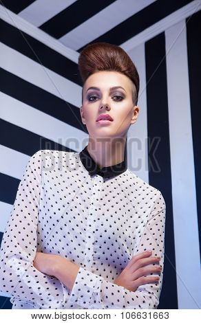Attractive young elegant woman wearing formal polka dot shirt  on stripy background, beauty and fashion concept